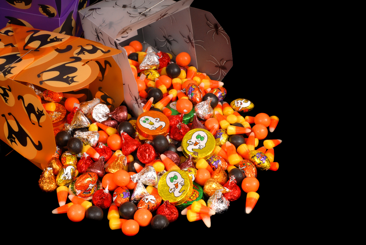 Image of three boxes with halloween pics toppled over with brown, orange, yellow, read candies spilled out including candy corns.